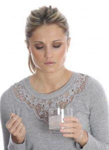 женщина употребляет таблетку